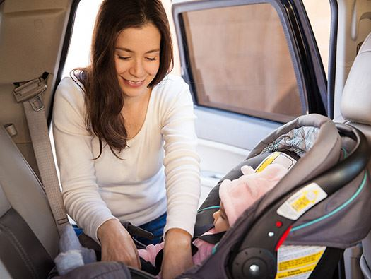 Woman Putting Child in Car Seat Photo