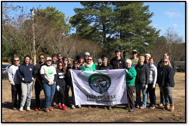Image of volunteers holding Tree City USA banner.
